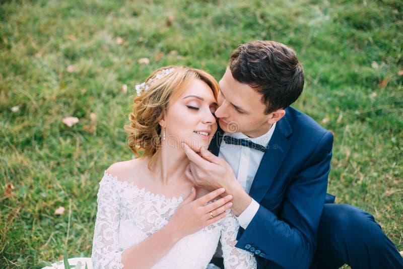 令人惊讶的有吸引力的年轻夫妇在婚礼那天 一件逗人喜爱的白色礼服的新娘,一蓝色时兴的新郎 免版税库存图片