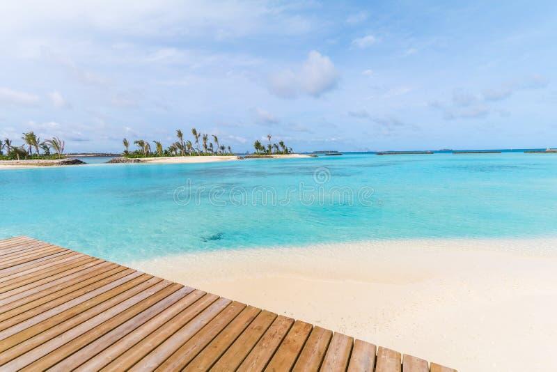 令人惊讶的海岛在马尔代夫、木桥和美丽的绿松石水域中有天空蔚蓝背景为假日假期 免版税图库摄影