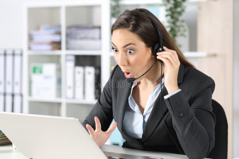 令人惊讶的电话营销人员在办公室阅读笔记本电脑新闻 库存照片