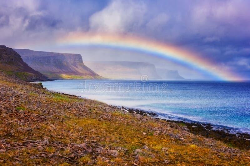 令人惊讶的自然、风景白天风景与彩虹在海洋,峭壁和剧烈的多云天空,大西洋岸,冰岛 免版税库存照片
