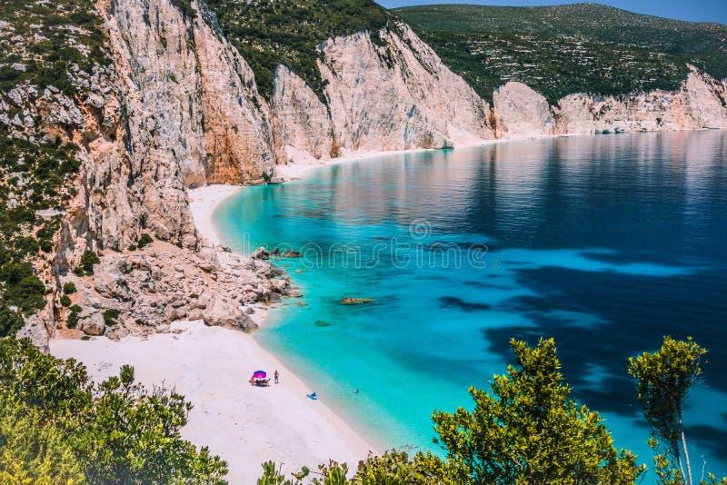 令人惊讶的Fteri使盐水湖, Kefalonia,希腊靠岸 在伞冷颤下的游人在清楚的蓝色鲜绿色绿松石海附近放松 免版税库存图片