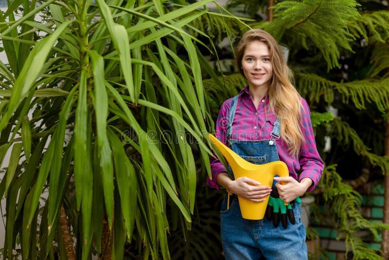 令人敬畏的快乐的女孩站立与一把喷壶 免版税库存图片