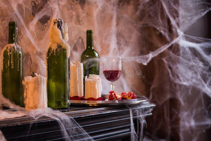令人毛骨悚然的蜘蛛网用蜡烛盖了在被困扰的议院设置的瓶和Candelabras 内部和装饰为 免版税库存图片
