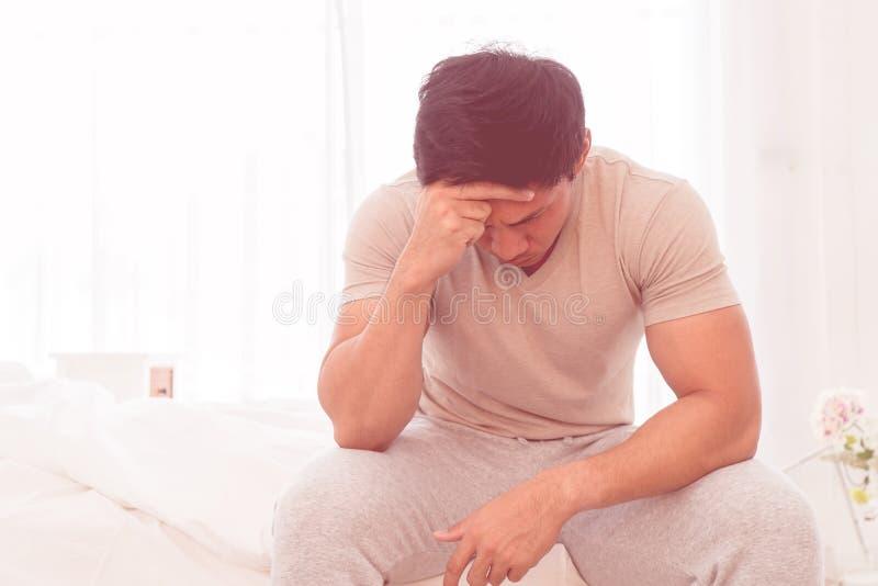 令人沮丧的人在与头疼的床上选址 免版税库存图片