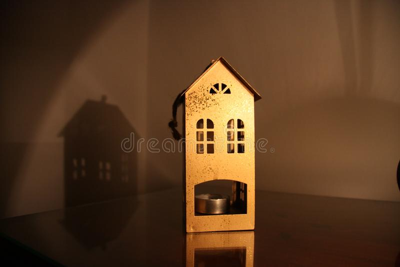以一个房子的形式金属烛台在桌上在与灯光的黑暗的晚上 库存图片