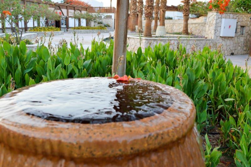以一个棕色花瓶,有水下跌的滴的一个水罐的形式一个美丽的小的喷泉在色的石头站立的 库存照片