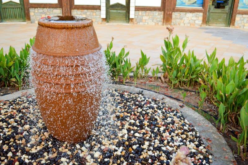 以一个棕色花瓶,有水下跌的滴的一个水罐的形式一个美丽的小的喷泉在色的石头站立的 免版税图库摄影