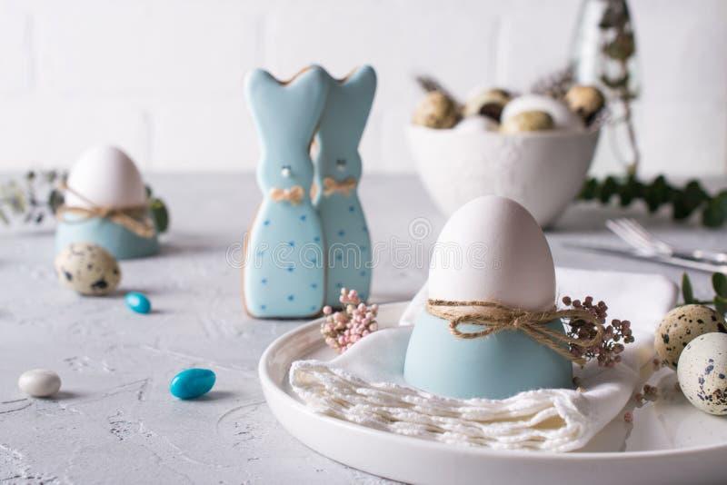 以一个滑稽的兔宝宝、鹌鹑蛋和鸡的形式自创复活节曲奇饼怂恿 复活节庆祝桌设置 免版税图库摄影