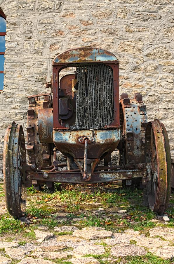 以一个灰色石墙为背景的被放弃的生锈的被转动的拖拉机 正面图 库存图片