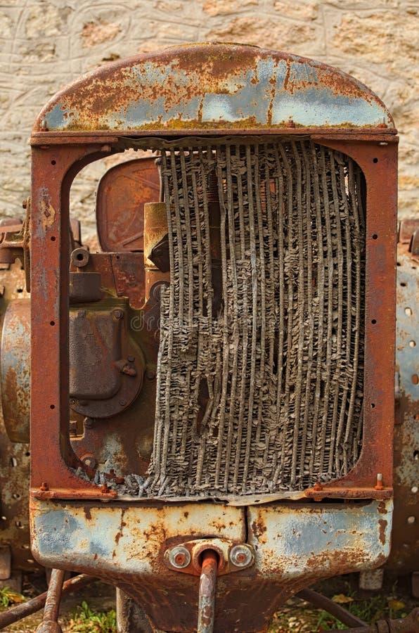 以一个灰色石墙为背景的被放弃的生锈的被转动的拖拉机 被毁坏的幅射器看法  库存照片
