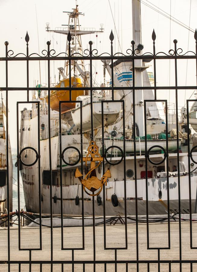 以一个船锚为特色有船被弄脏的背景的海口篱芭  r 免版税库存照片