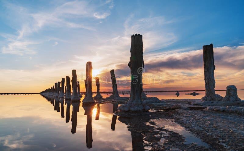 以一个门的形式木被风化的岗位盐提取的在盐湖中桃红色水有蓝天的在乌克兰 库存照片