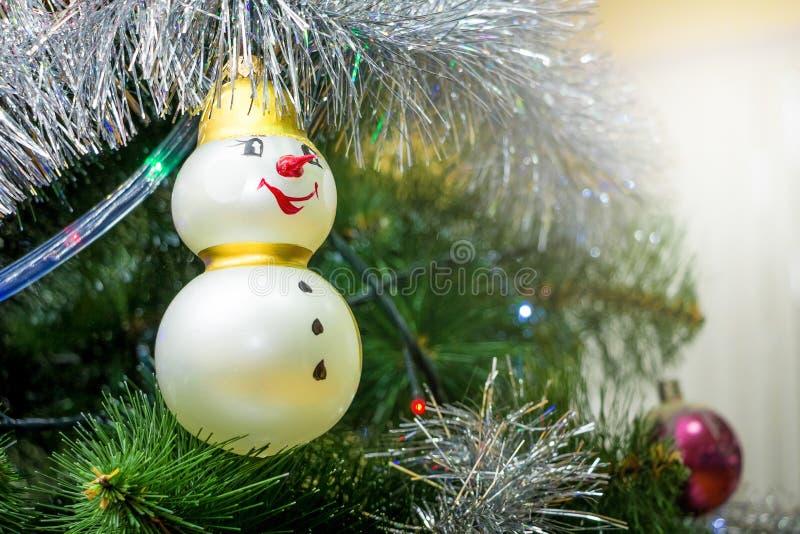 以一个雪人的形式明亮的装饰在圣诞树 库存图片