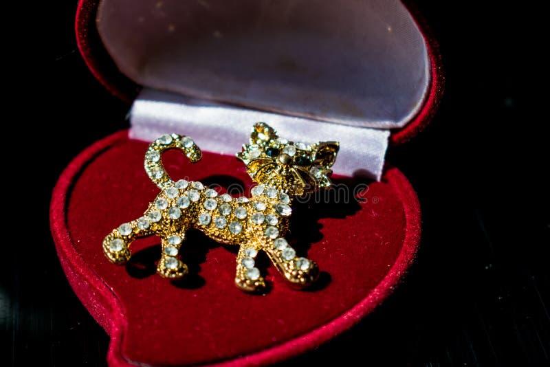 以一只小猫或一只虎犊的形式金属金黄别针与白色石头,假钻石 在一黑光滑,反射性backgroun 库存图片