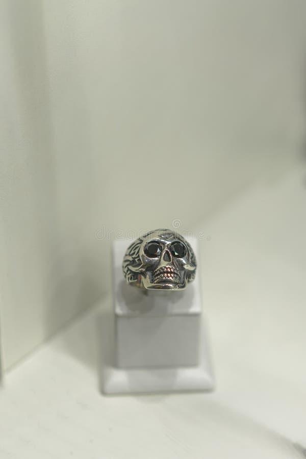 以一块头骨的形式银色圆环在一个风帆在商店 ertical?? 库存照片