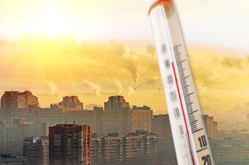 以一阵被污染的城市烟雾为背景的温度计在热天气期间 库存图片