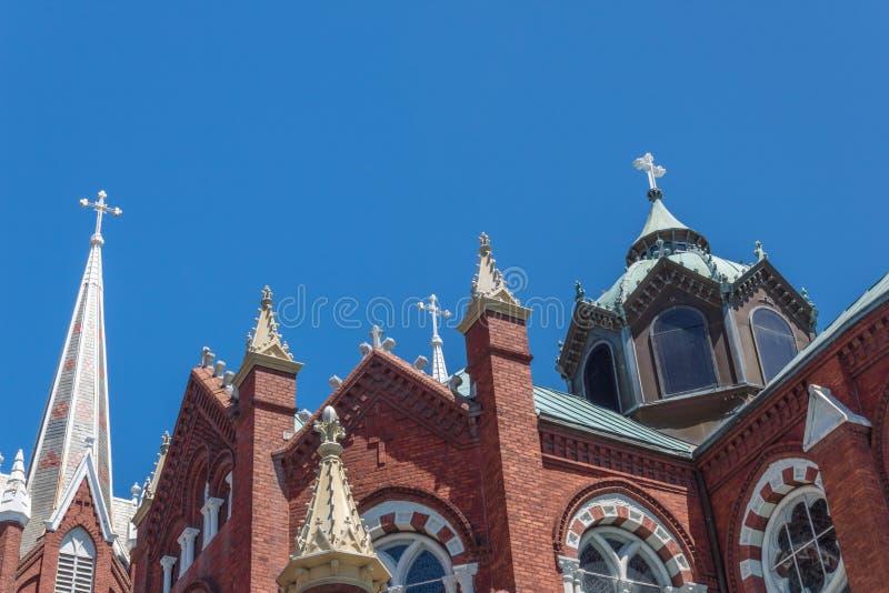 以三个白色十字架为特色的一个哥特式复兴教会的华丽尖顶、圆顶和窗口反对天空蔚蓝 库存图片