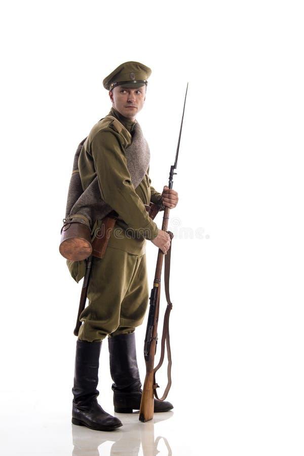 以俄国军队的一位普通的战士的形式男性演员在摆在反对白色背景的第一次世界大战期间的  库存图片