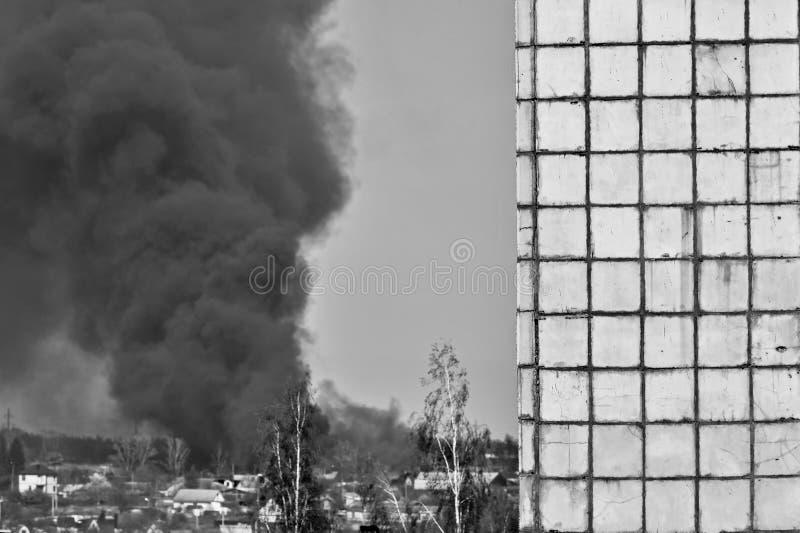 以修造的墙壁的形式模板反对天空和厚实的黑烟 黑色白色 库存图片