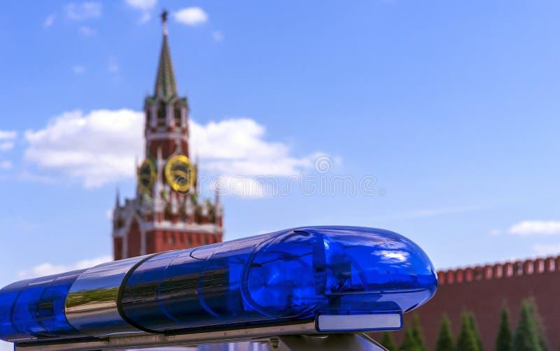 以克里姆林宫为背景的蓝色警笛在莫斯科 在Spasskaya塔的背景的警察敷金属纸条  库存照片