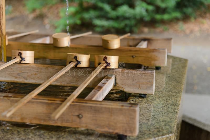 以前浸洗洗涤的仪式的杯子,手洗涤亭子输入寺庙门在美济礁jingu在东京,日本 宗教和 免版税库存图片