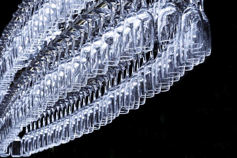 以卵形吊的形式很大数量的玻璃在酒吧柜台的持有人在黑暗的背景 免版税库存照片