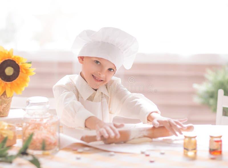 以厨师的形式小男孩在厨房里铺开面团 库存图片
