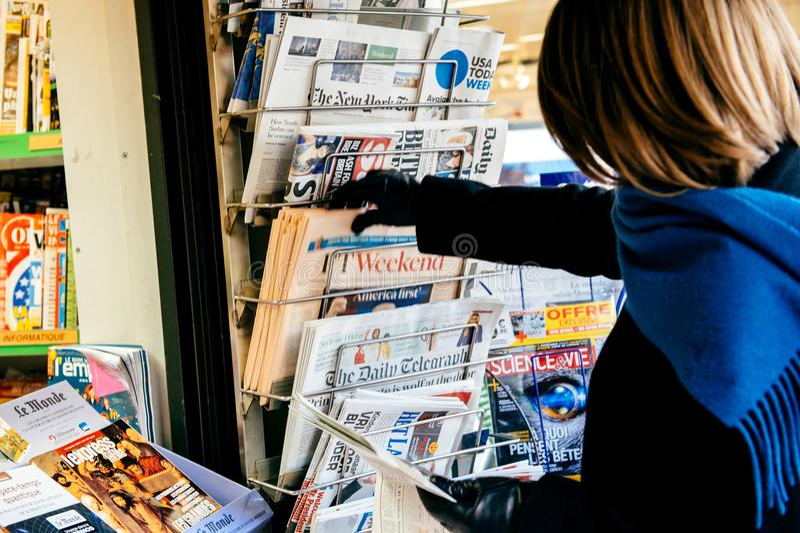 以唐纳德・川普Americ为特色的金融时报的妇女购物 免版税库存照片