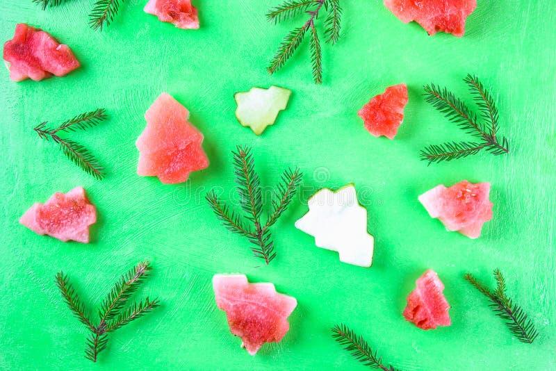 以圣诞树的形式西瓜与在绿色背景的云杉的分支 平的位置 顶视图 免版税库存照片