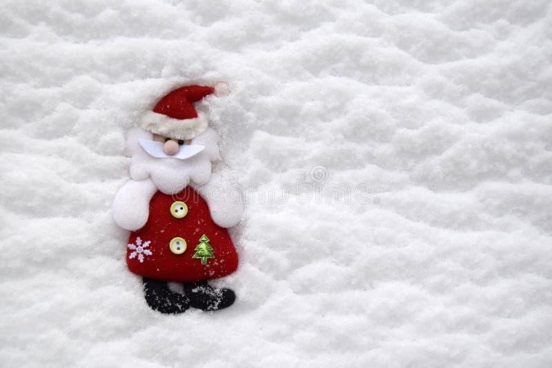 以圣诞老人项目的形式圣诞节软的玩具位于以白色自然雪为背景 免版税库存图片