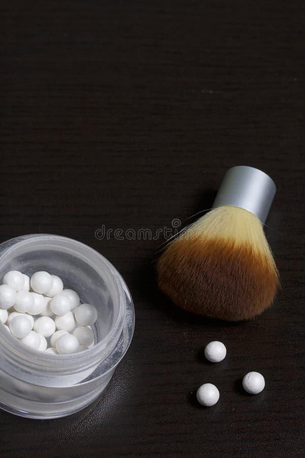 以在一个开放瓶子的球的形式成珠状轮廓色_ 接近应用的化妆用品刷子 几个球说谎并行的o 库存图片