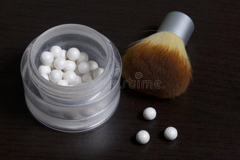 以在一个开放瓶子的球的形式成珠状轮廓色_ 接近应用的化妆用品刷子 几个球说谎并行的o 免版税库存照片
