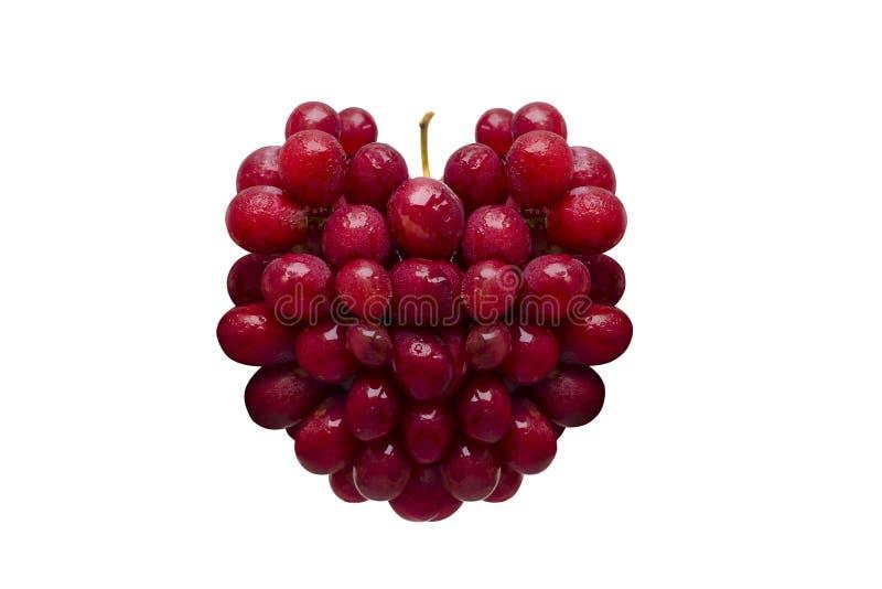 以在白色背景隔绝的心脏的形式新鲜的红葡萄 免版税库存照片