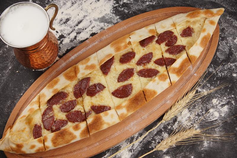 以小船的形式土耳其薄饼在牛奶ayran旁边一份全国饮料称一染色,被冠上的被烘烤的sudzhuk, 图库摄影