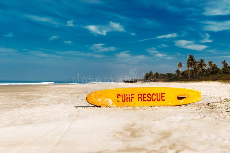 以尖的形式明亮的黄色冲浪板与在一个沙滩的红色词抢救下午 黄色的救生 免版税图库摄影