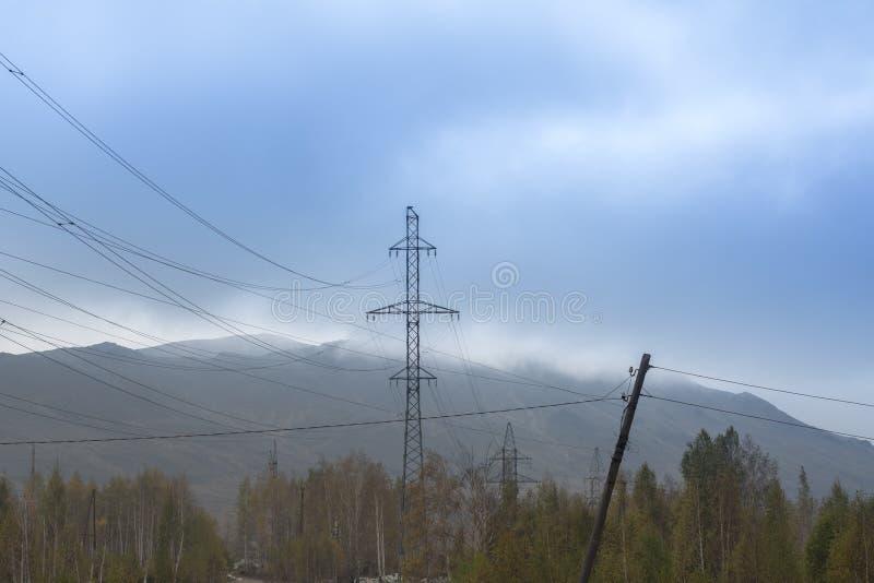 以山为背景的高压杆在雾 免版税库存照片