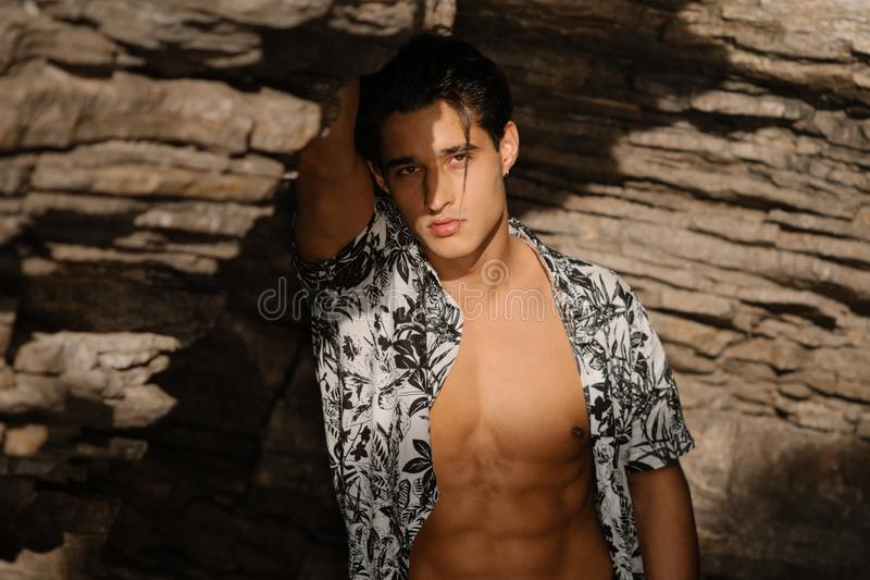 以岩石为背景的年轻有吸引力的人立场在海附近 在岸的男性模型 库存照片