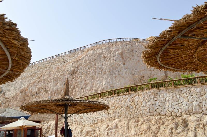 以帽子的形式美丽的盖的秸杆伞在一片热带沙漠依靠以岩石和一石wa为背景 免版税库存照片