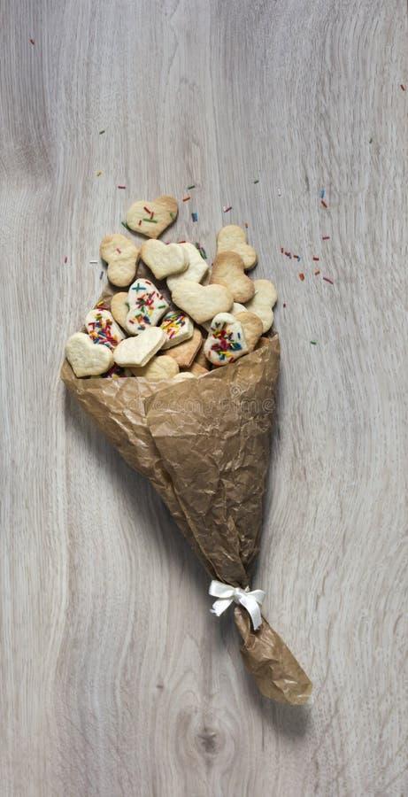 以心脏和多彩多姿的形式,在一张木桌上是袋子被弄皱的纸用曲奇饼 免版税库存照片