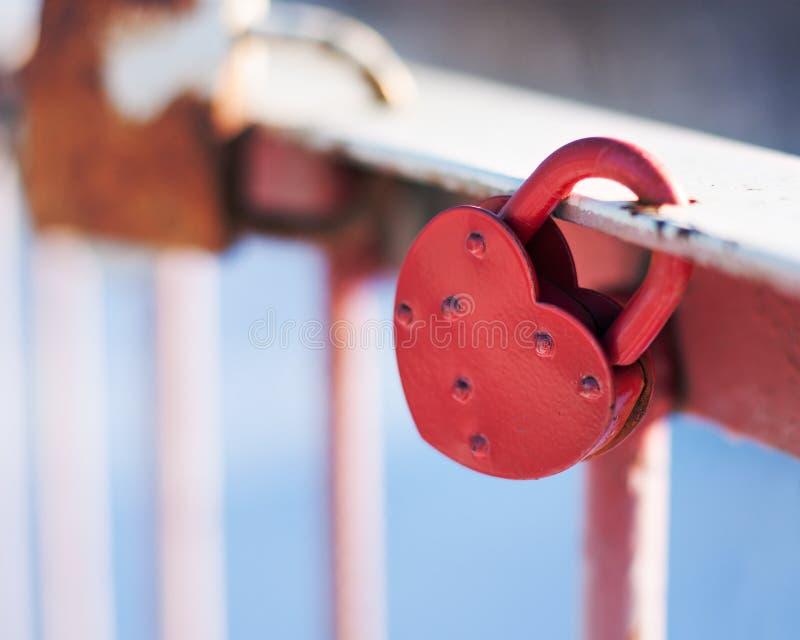 以心脏的形式一把锁在老桥梁的路轨垂悬 垂悬的锁作为爱和忠诚的标志 免版税库存图片