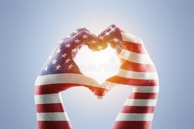 以心脏的形式两只手与美国旗子 图库摄影