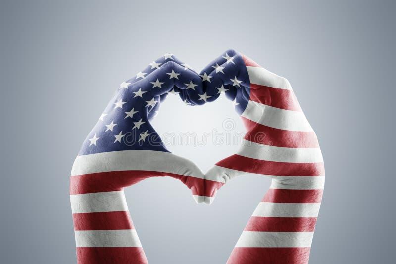 以心脏的形式两只手与美国旗子 库存图片