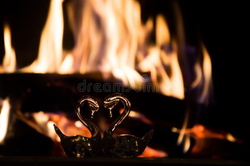 以心脏的形式两只玻璃天鹅在壁炉附近 免版税图库摄影