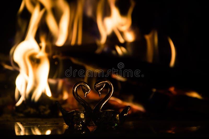 以心脏的形式两只玻璃天鹅在壁炉附近 免版税库存照片