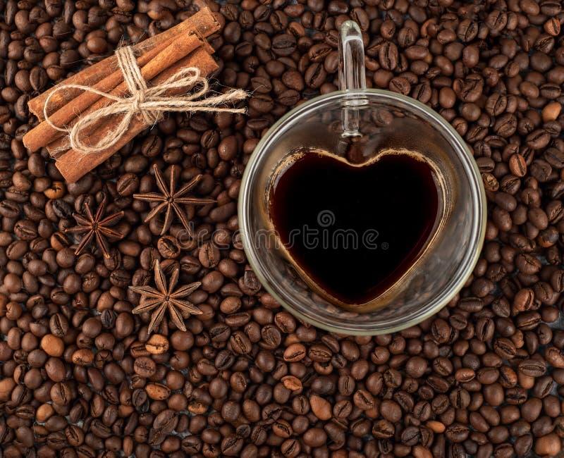 以心脏的形式咖啡杯在咖啡豆用桂香a 库存图片