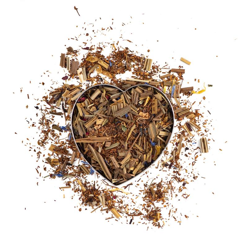 以心脏的形式清凉茶堆在白色背景 薄菏,柠檬香茅,矢车菊,玫瑰花瓣 顶视图 库存图片