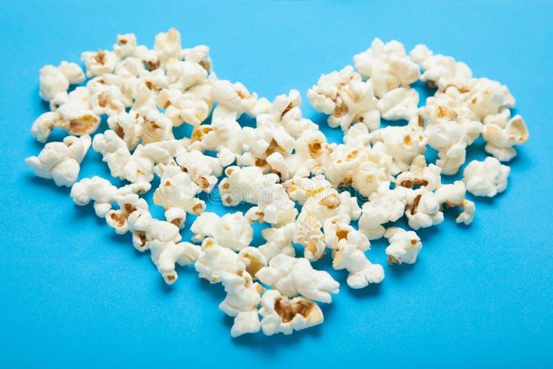 以心脏的形式玉米花在蓝色背景 免版税库存照片