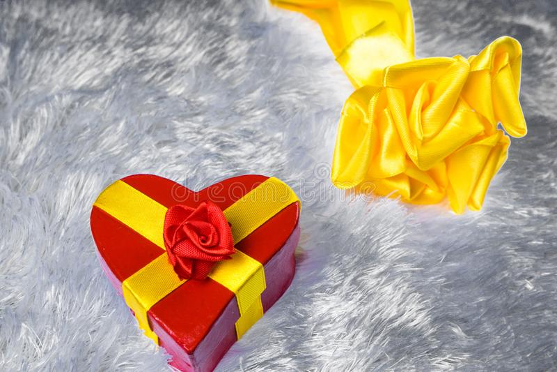 以心脏的形式礼物盒栓与与弓的一条黄色丝带以玫瑰的形式在枕头伪造品毛皮说谎和其次 免版税图库摄影