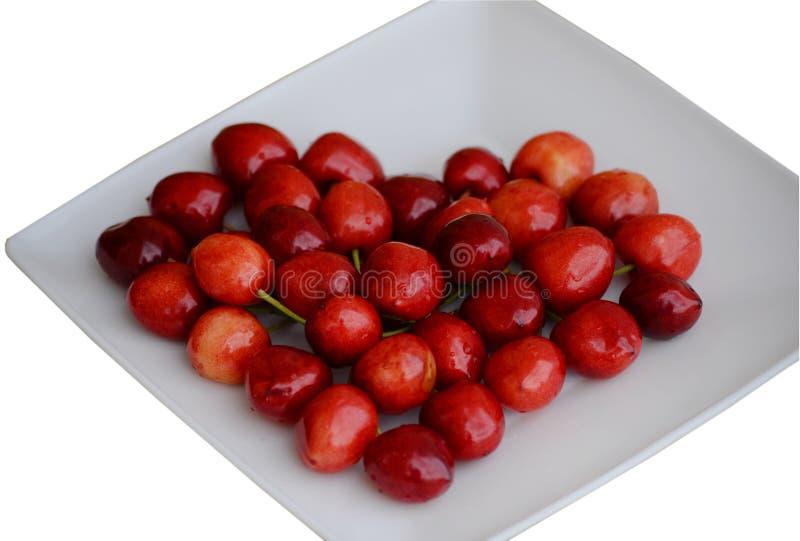 以心脏的形式美丽的湿红色樱桃在一块白方块板材 免版税库存图片