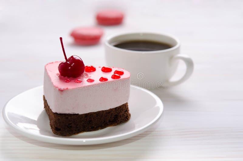 以心脏的形式蛋白牛奶酥蛋糕与咖啡和蛋白杏仁饼干在木桌上 免版税库存照片